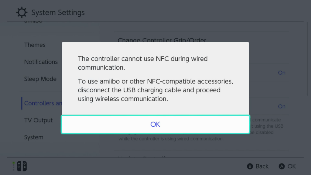 Screen shot showing a warning message on the Nintendo switch after Pro Controller Wired Communication has been selected, with OK highlighted to accept the warning for selection. The full message reads The controller cannot use NFC during wired communication. To use the amiibo or other NFC-compatible accessories, disconnect the USB charging cable and proceed using wireless communication.