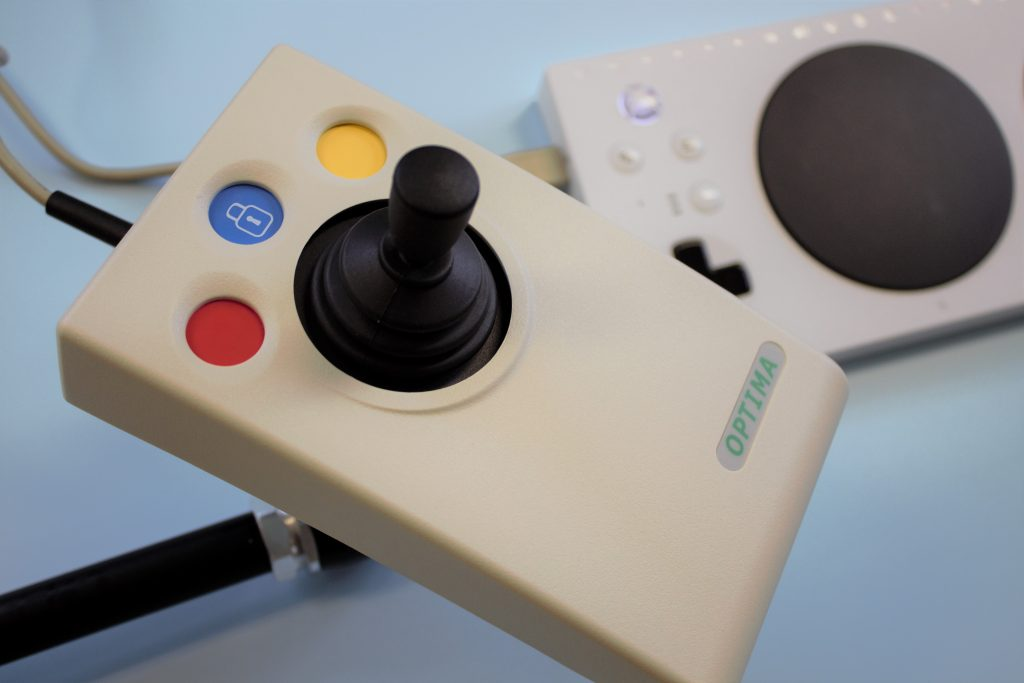 Photo showing Optima joystick mounted above an Xbox Adaptive Controller with a Manfrotto variable Friction Arm.