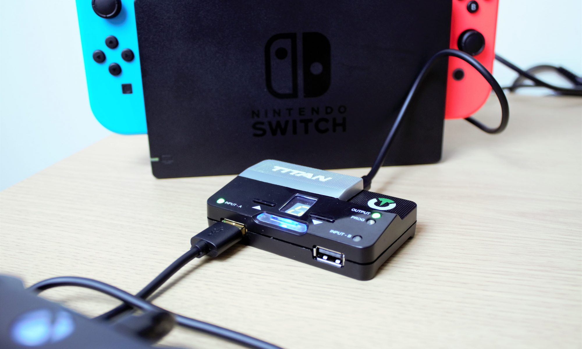 Photograph showing a Titan Two adapter connect to a Nintendo Switch in it's dock and with a corner of an Xbox One controller in the forground of the picture which is connected to the Titan Two.