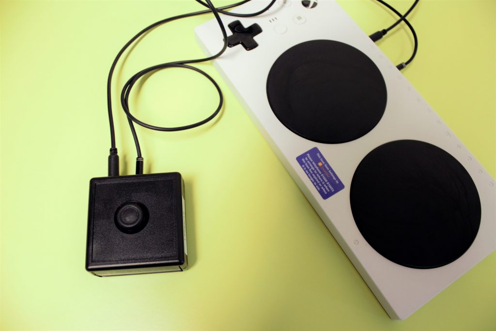 the analog sticki in small ba;lck plastic case of the XAC Mini Joystick pluuged into the Xbox Adaptive Controller.