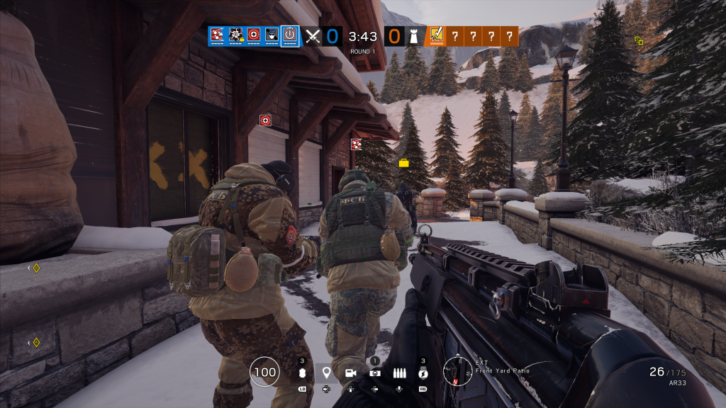 Screenshot showing a squad approaching a building in a mountanous location with pine tress and snow covered ground. Windows are barricaded with wood.