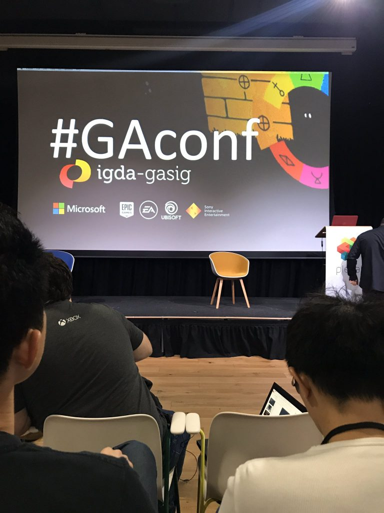 Third row view of the IGDA GASIG Game Accessibility conference stage, in London.