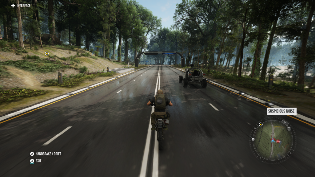 Screenshot of Ghost Recon Breakpoint showing a 3rd person view of a someone on a motorcyle on a tarmac road in a wooded area passing by an all-terrain vehicle.