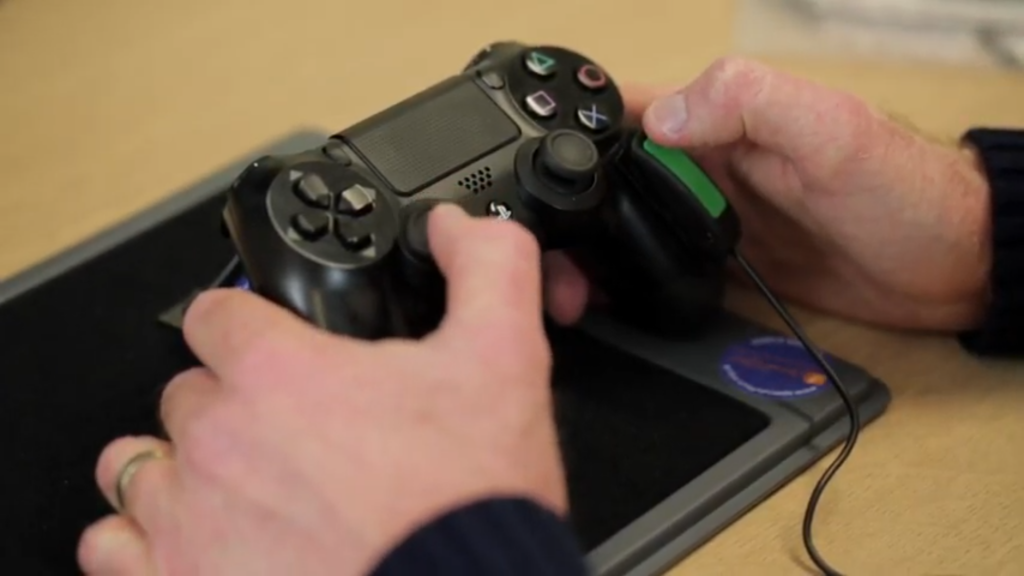 """An image showing a still from the video above of an Ultra Light HD Switch being mounted onto a PS4 controller."""