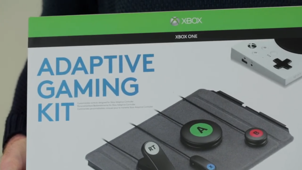 """An image showing a still from the video above of an Adaptive Gaming Kit being held."""