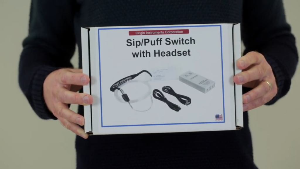 """An image showing a still from the video above of a Sip and Puff switch being held."""