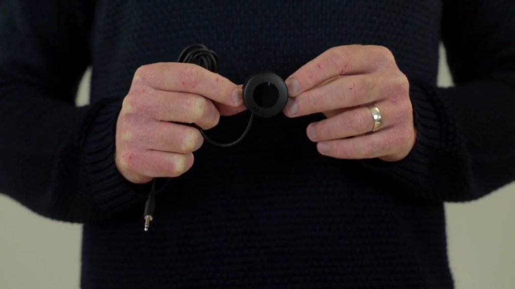 """An image showing a still from the video above of a Small Button being held."""
