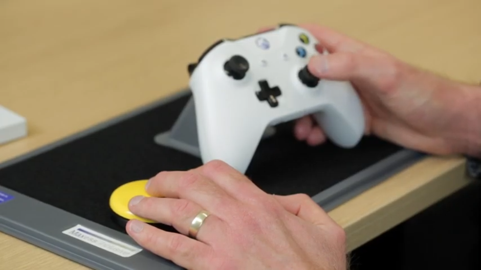 """An image showing a still from a SpecialEffect video of an Xbox One controller mounted on a Maxess wedge and a Maxess tray."""