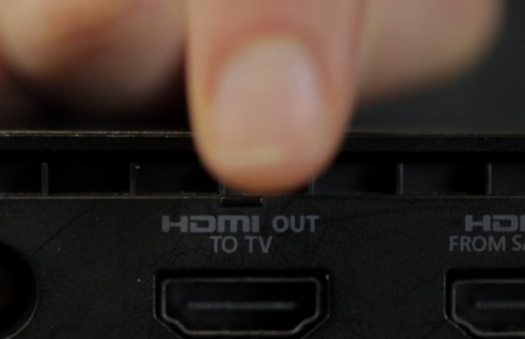 "Finger pointing to ""HDMI OUT TO TV"" socket on back of Xbox One console."