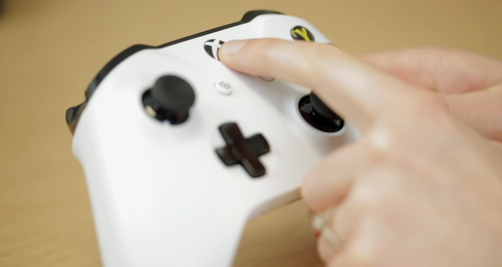 "Finger pressing ""home"" button on an Xbox One controller."
