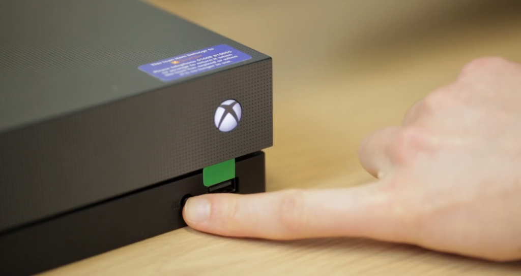 Finger pressing sync button on front of Xbox One console.