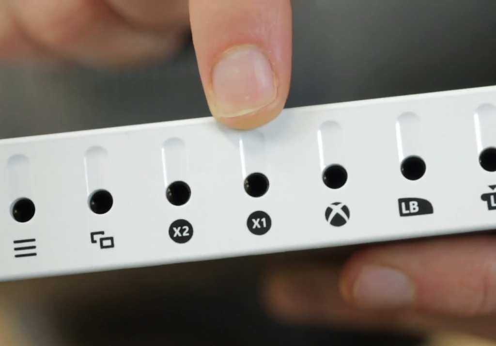 Finger pointing at X1 and X2 socket on the back of the Xbox Adaptive controller.