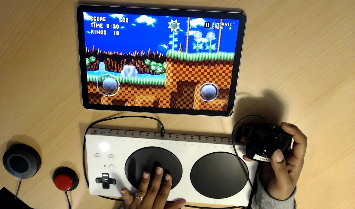Example of an Xbox Adaptive Controller (XAC) set up with an iPad with peripherals connected for joysticks and button inputs. These peripherals include an XAC Flat Thumbstick from Evil Controllers, a Logitech Medium Switch and a Specs switch playing Sonic the Hedgehog Classic.