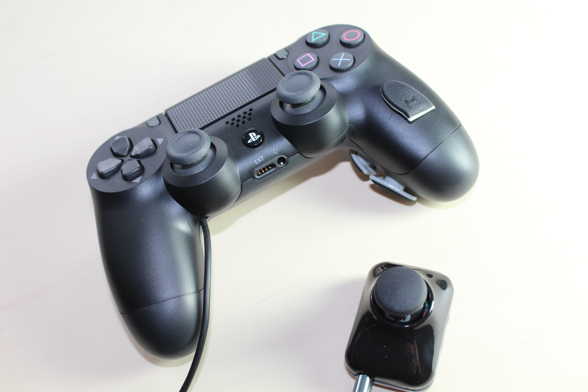 PS4 'Righty' Controller with the extension option for the left thumbstick next to it. Three additonal buttons are on the right hand grip.