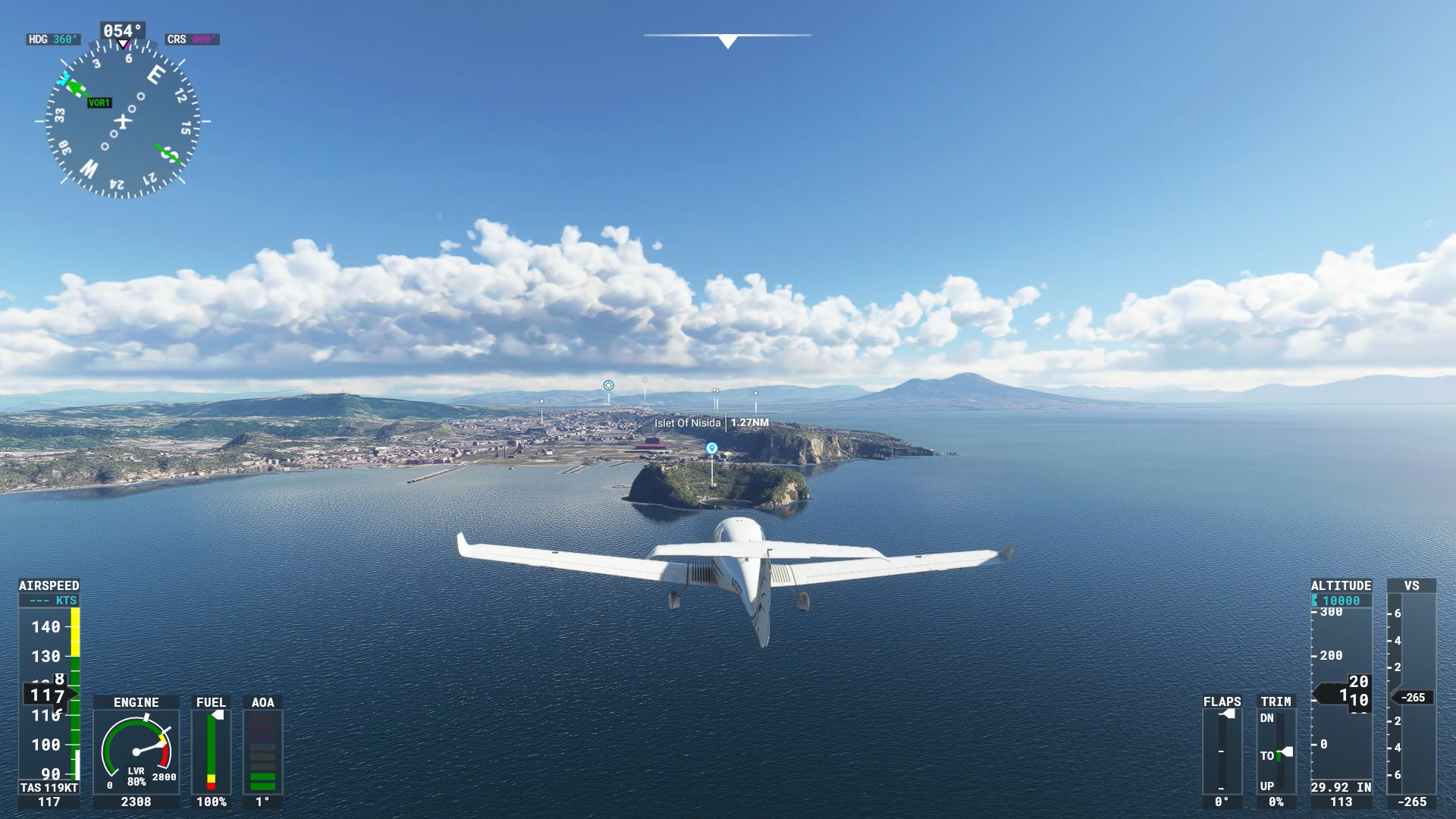 Small aircraft shown from behind flying over sea towards land.