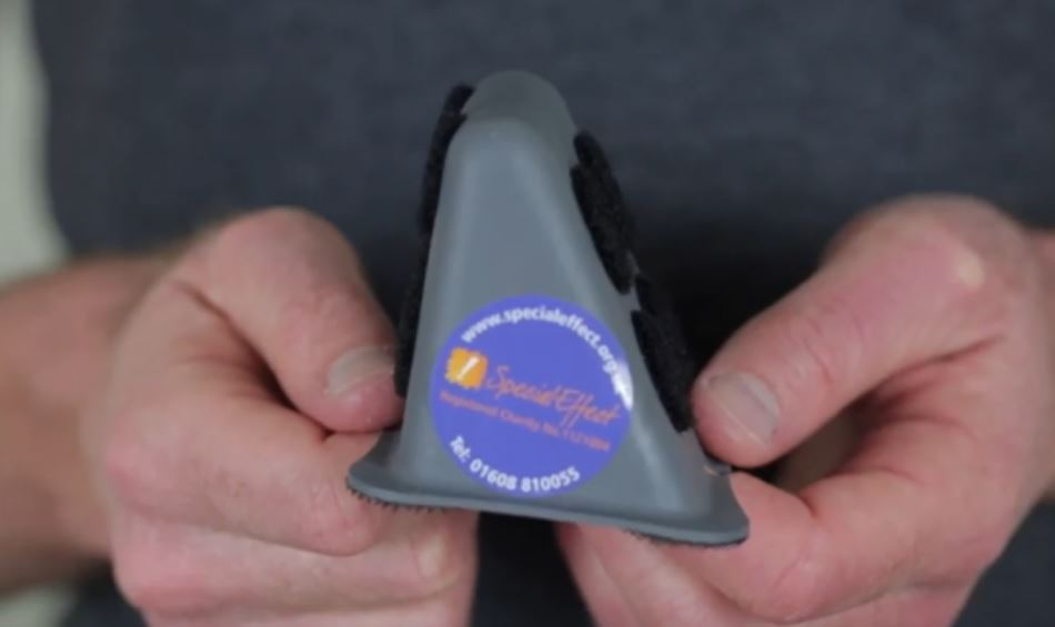 A photograph of a small Maxess mount being held.